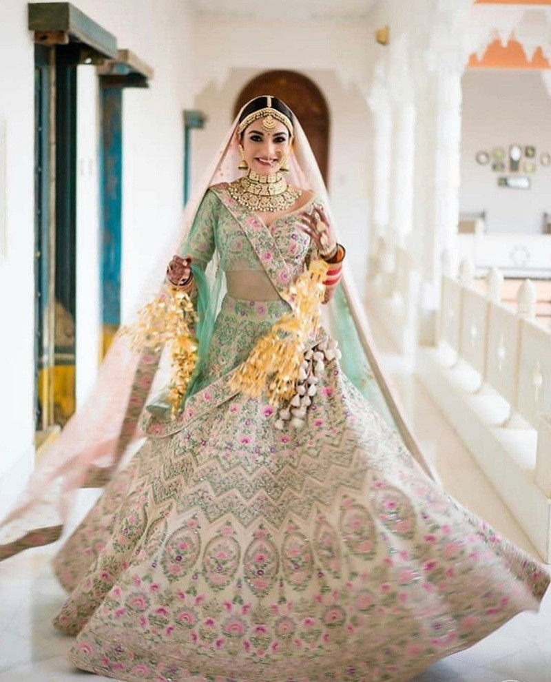 4. An ivory based lehenga choli with multi pink, yellow and red-colored work on it