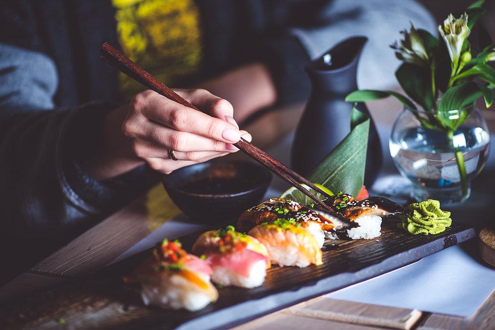 Man eating sushi set with chopsticks on