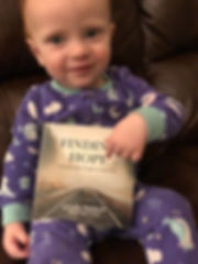18-month old girl holding Finding Hope