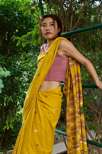 A woman a yellow and maroon saree leaning against a green hedge