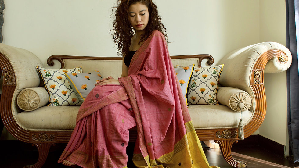 A girl wearing a beautiful pink silk saree sitting on a couch