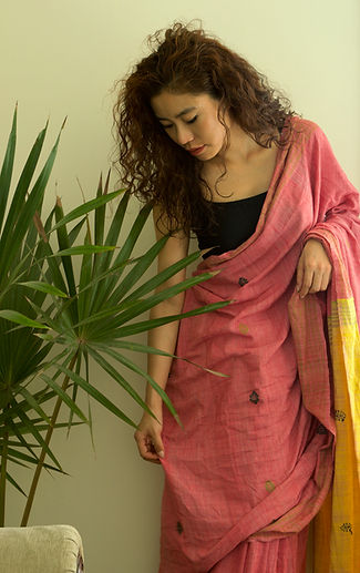 A curly haired women wearing a pink silk saree standing against a wall next to a green potted palm plant