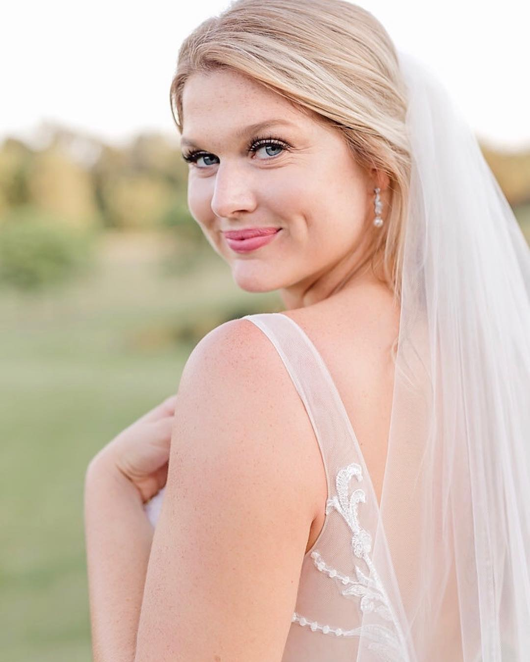A bride looks over her shoulder at the camera, makeup done by artist Melina Tobin