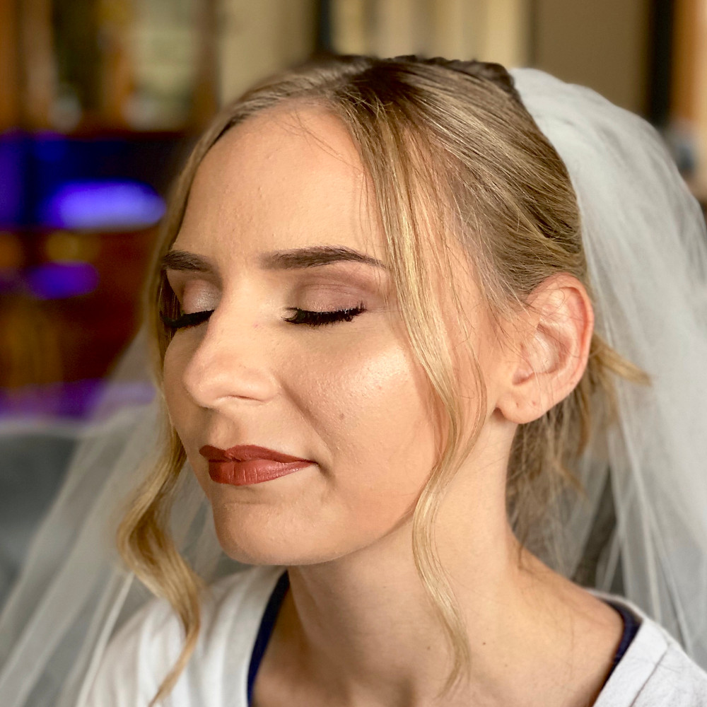 Bride with flawless makeup. Her eyes are closed and she is wearing a veil