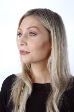Striking blonde woman with makeup done by artist Melina Tobin