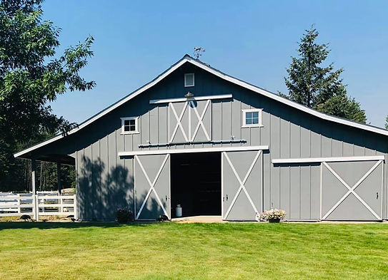 Two story barn in grey color with white accents with front doors open