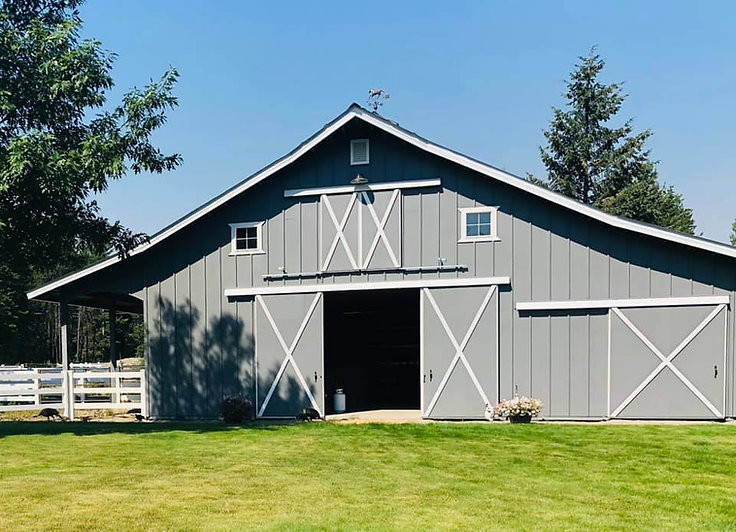 Grey with lighter colored accents barn with doors open front view