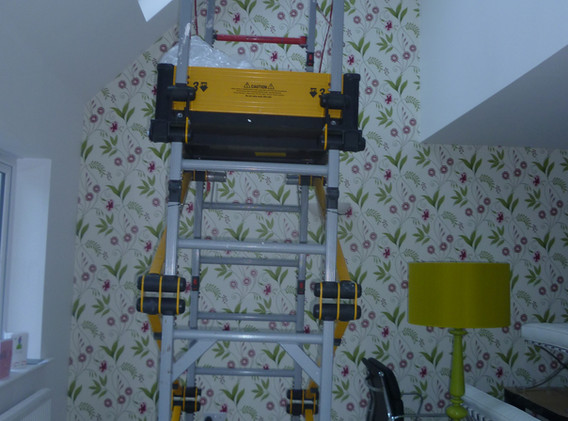 Wallpapering a double-height feature wall.