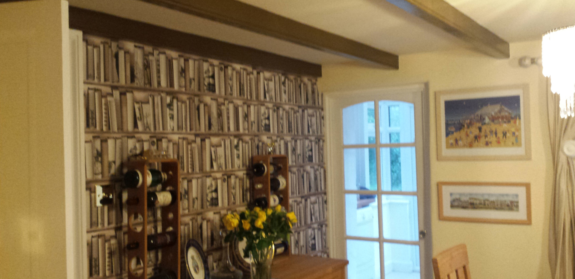 Dining room makeover with bookshelf feature wallpaper.