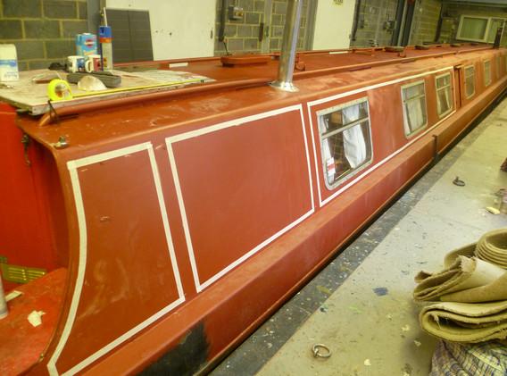 Narrowboat in red oxide primer.