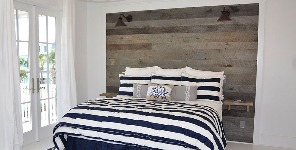 A bedroom with reclaimed oak wall planks colored weathered gray