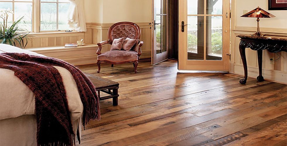 A bedroom with unfinished reclaimed oak flooring, hit/miss and skip sawn