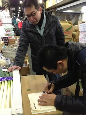 今朝の築地場内。自著『キレイゴトぬきの農業論』にサインする久松先生。興味津々で覗き込む政義青果、近藤社長。築地にも『エロうま野菜』の波が・・・いよいよ本格的に来る!・・・