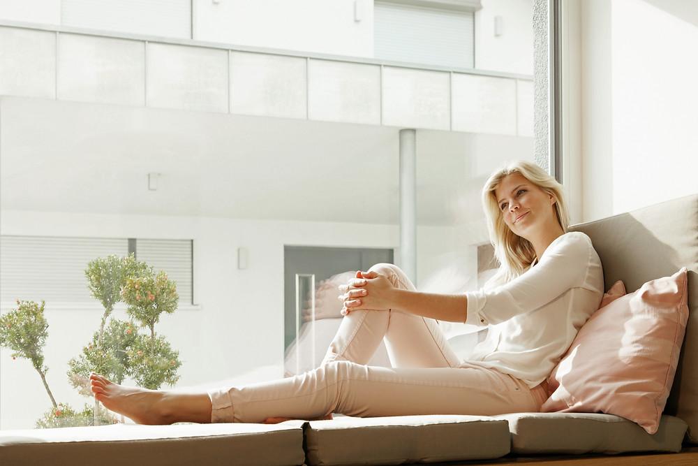 Eine Frau sitzt entspannt innen vor einem Panoramafenster.