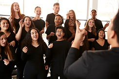 Male And Female Students Singing In Choir With Teacher At Performing Arts School.jpg