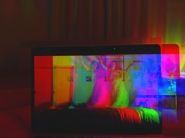 An open laptop screen. On the screen a person in a white fluffy skirt is dancing on their bed. The image splits into three, overlaying in bold RBG colours.
