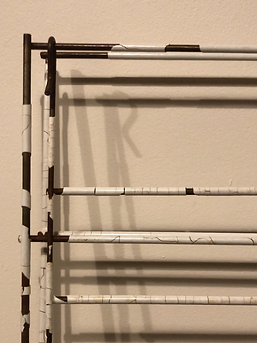 Close-up of clothes drying rack with white plastic coating cracked or fallen off