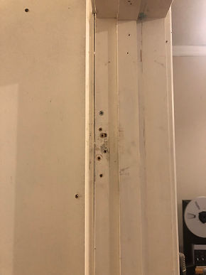 Two sets of three holes in a door frame from where a door was hinged multiple times