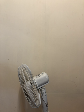 A drooping standing fan with writing that says good working order