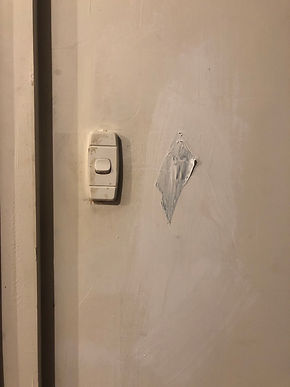 Next to a light switch, a piece of duct tape is stuck on the wall and roughly painted over with paint whiter than the wall's off-white