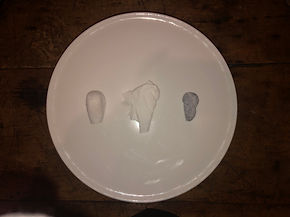 Top-down view of three objects in a row on a white platter