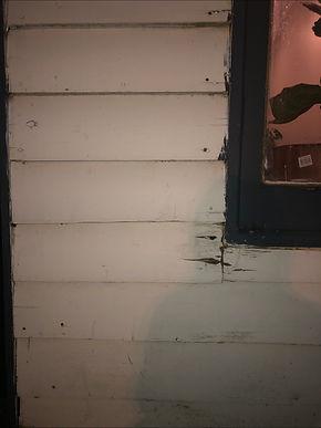 Wood below a window sill splintering. A person's shadow is cast over it.