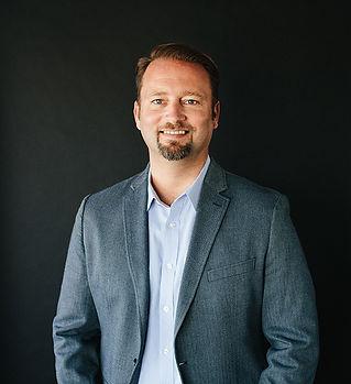 Photo of Daniel Bush in a blue grey sportcoat - smiling