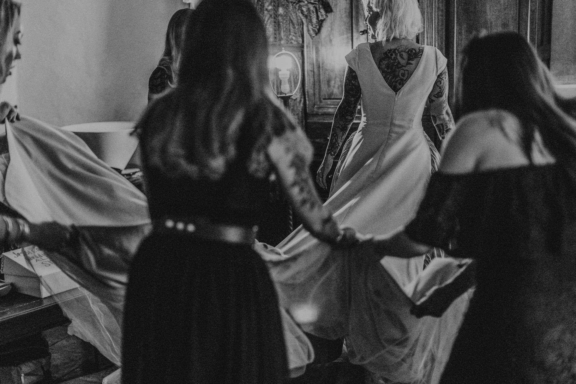 bridesmaids holding bride's train black and white