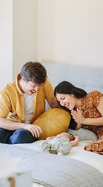 mom and dad playing with newborn baby on bed