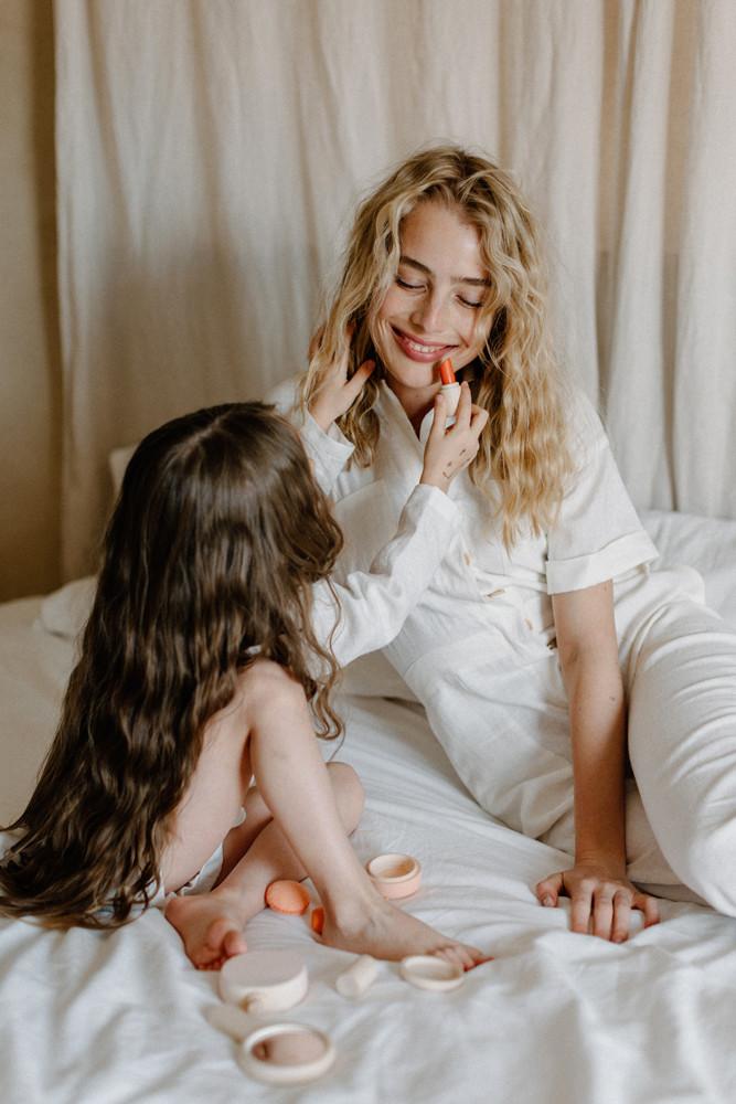 girl putting lipstick on mom lifestyle photoshoot