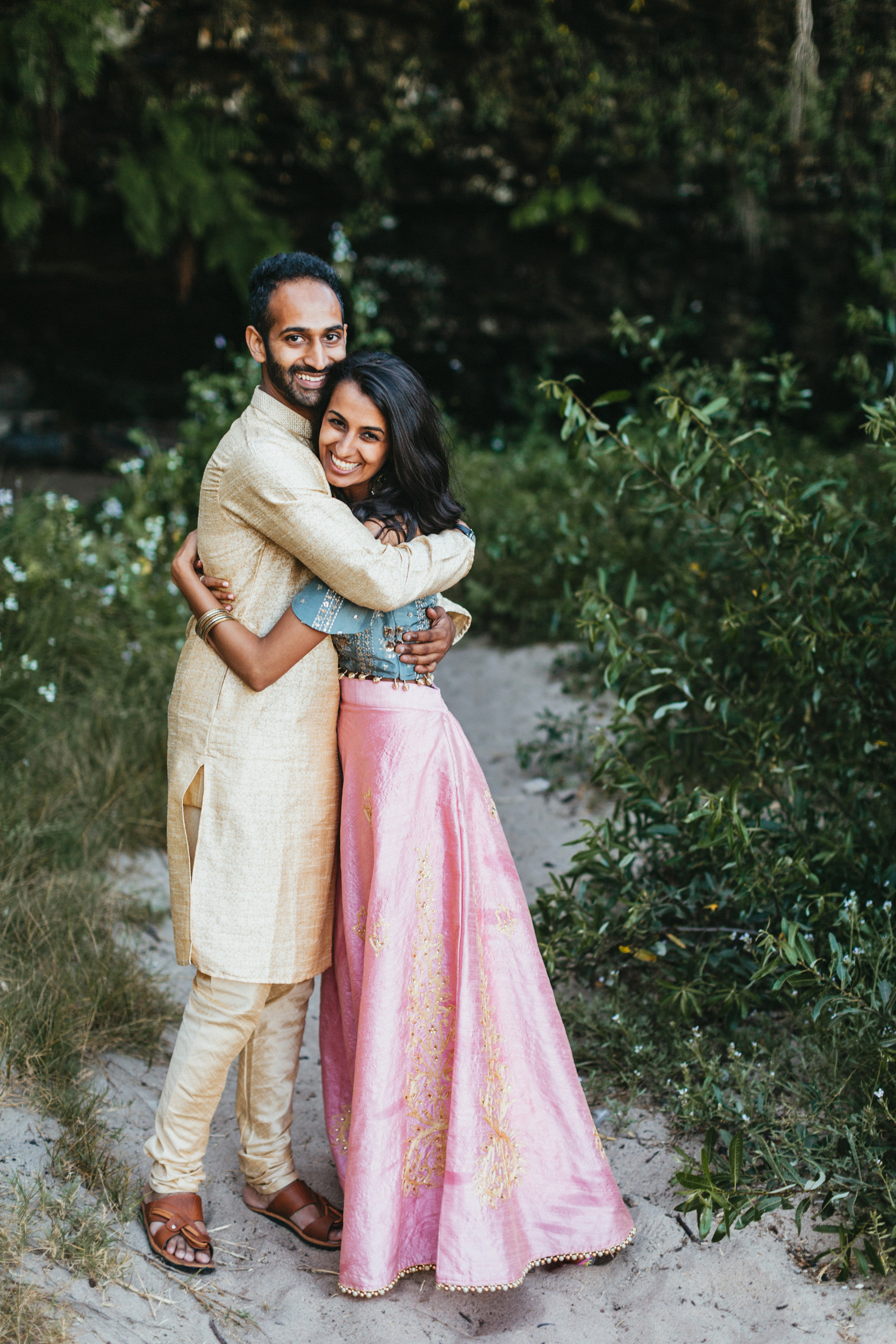 indian couple hugging on beach engagement session