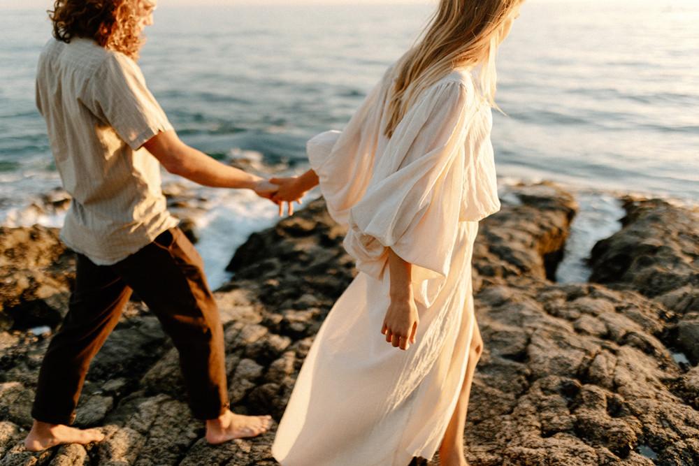 walking along cliffs laguna beach engagement photos