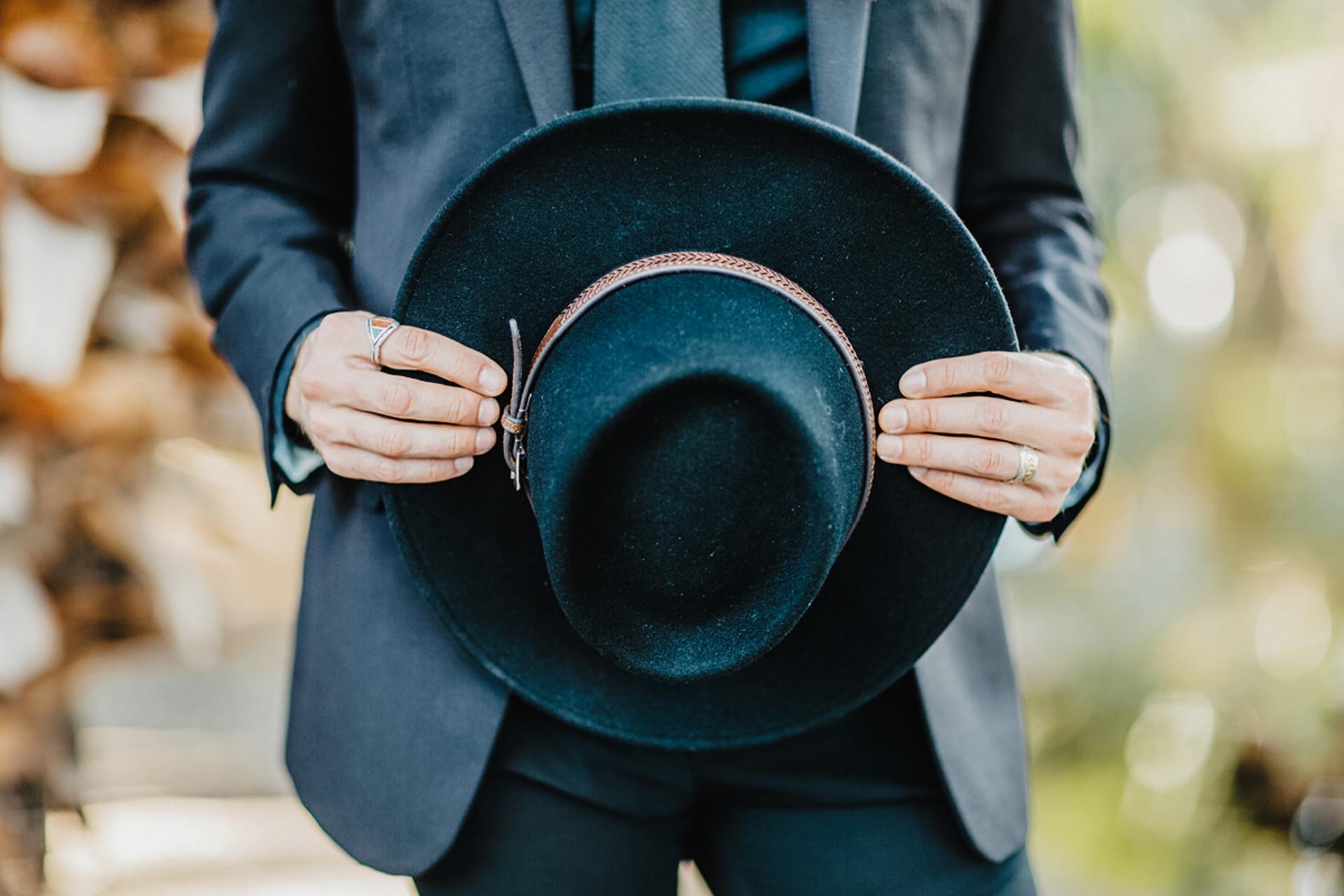 groom wearing all black holding hat