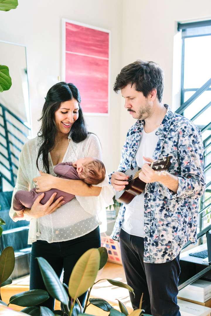 mom holding baby while dad plays guitar