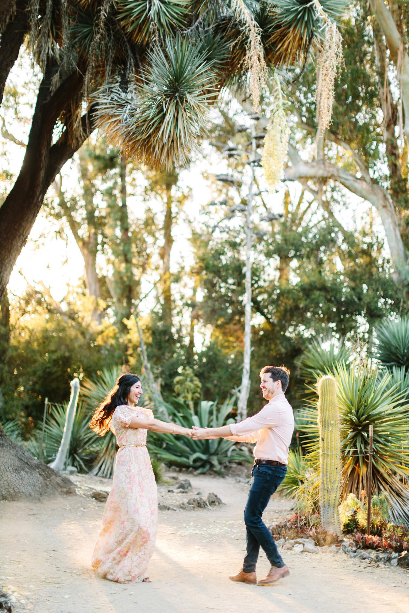 couple spinning around cactus garden engagement photos