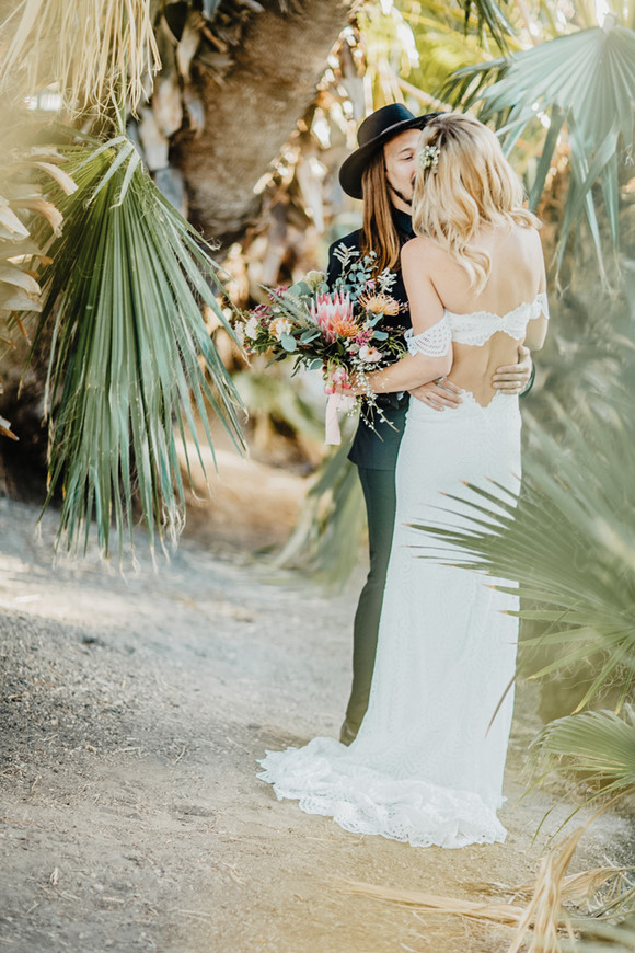 bride and groom dancing among palm trees