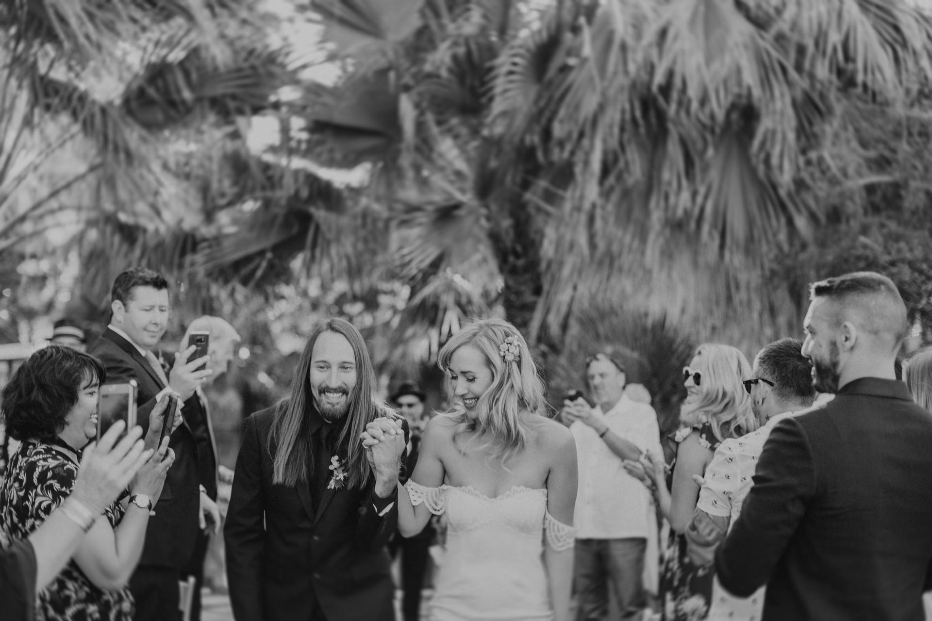 palm tree wedding couple walking down aisle