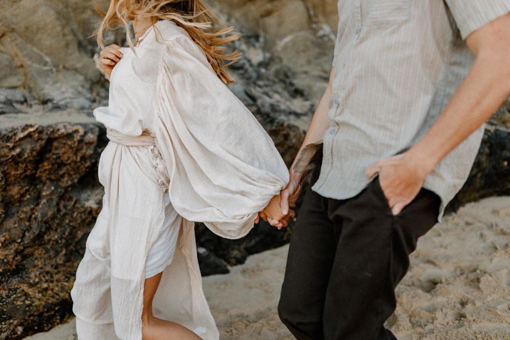 holding hands running along laguna beach