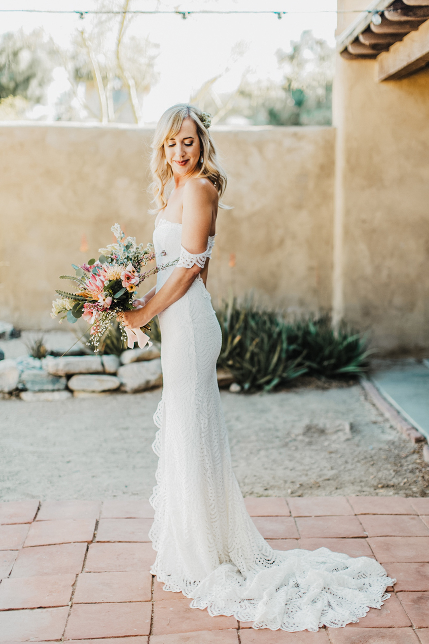 bride wearing off the shoulder wedding dress holding bouquet