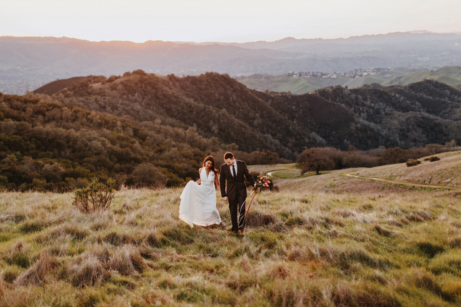 couple walking in field with rolling hills behind