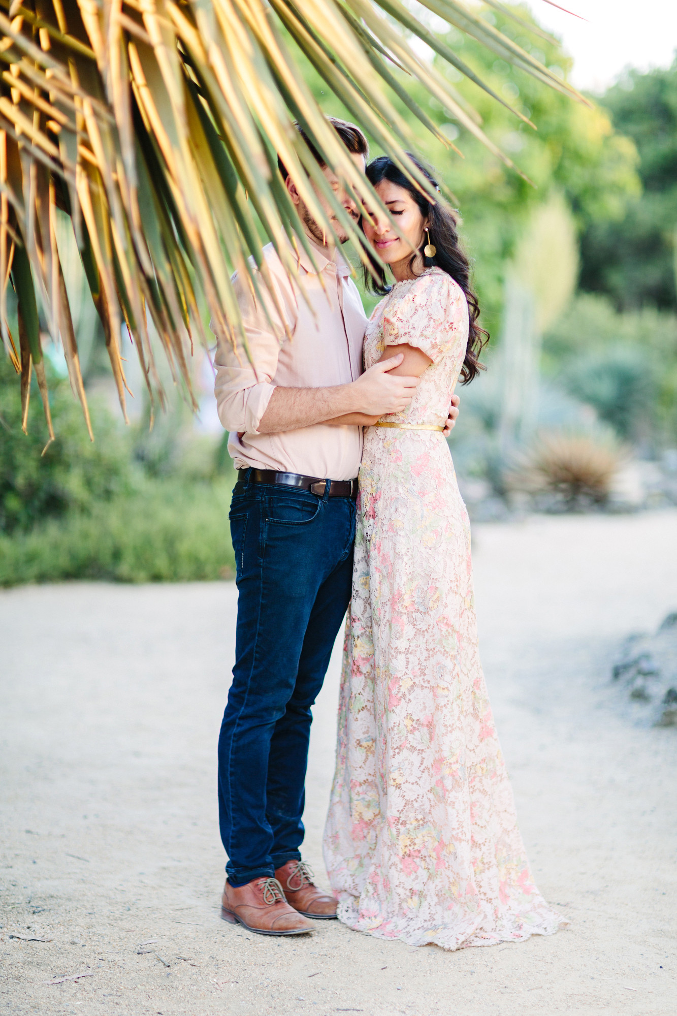 couple behind palm frond engagement photos
