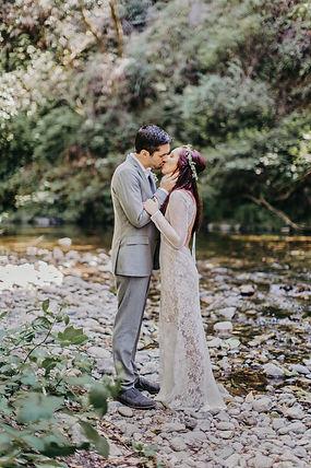 bride and groom kissing along creek glen oaks big sur