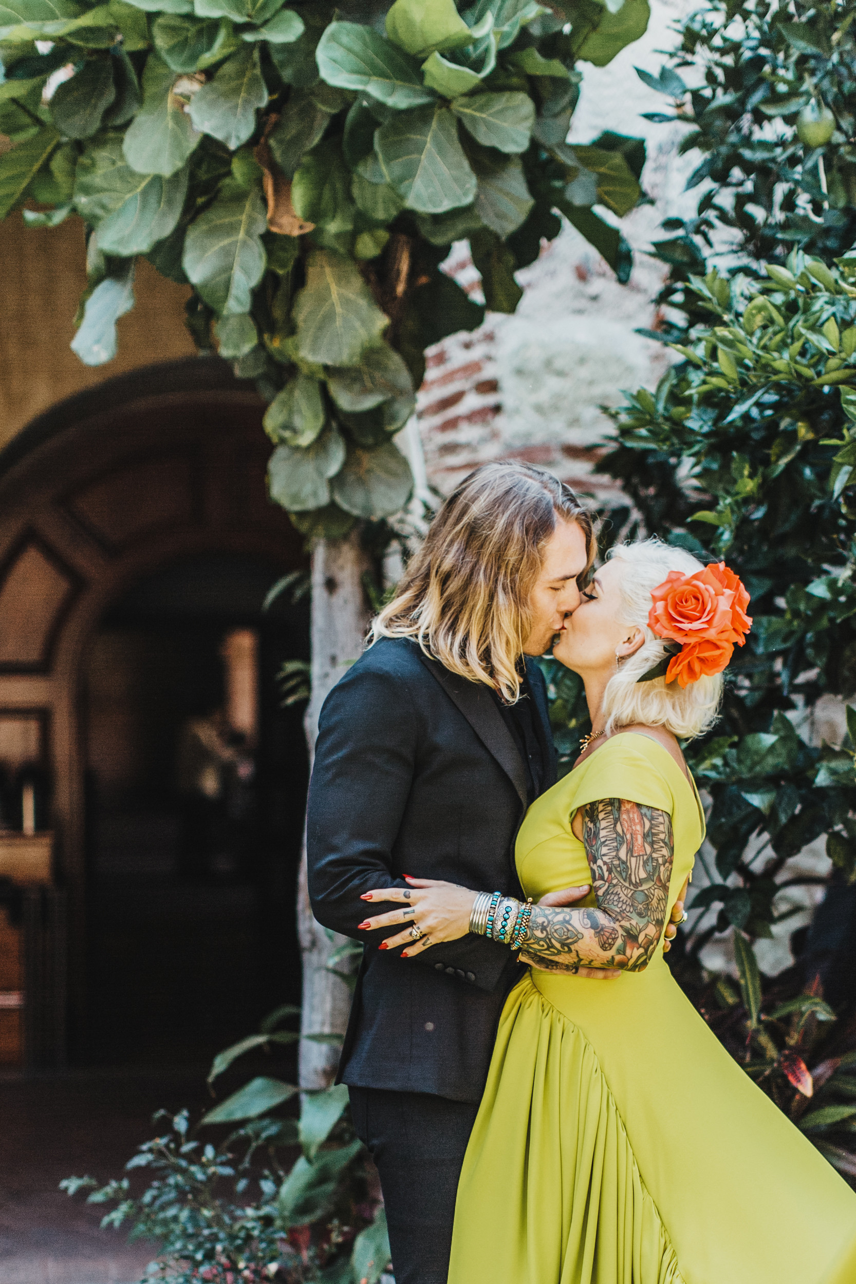 bride and groom kissing under fiddle leaf tree
