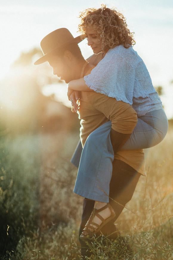 guy giving girl piggyback ride engagement photo
