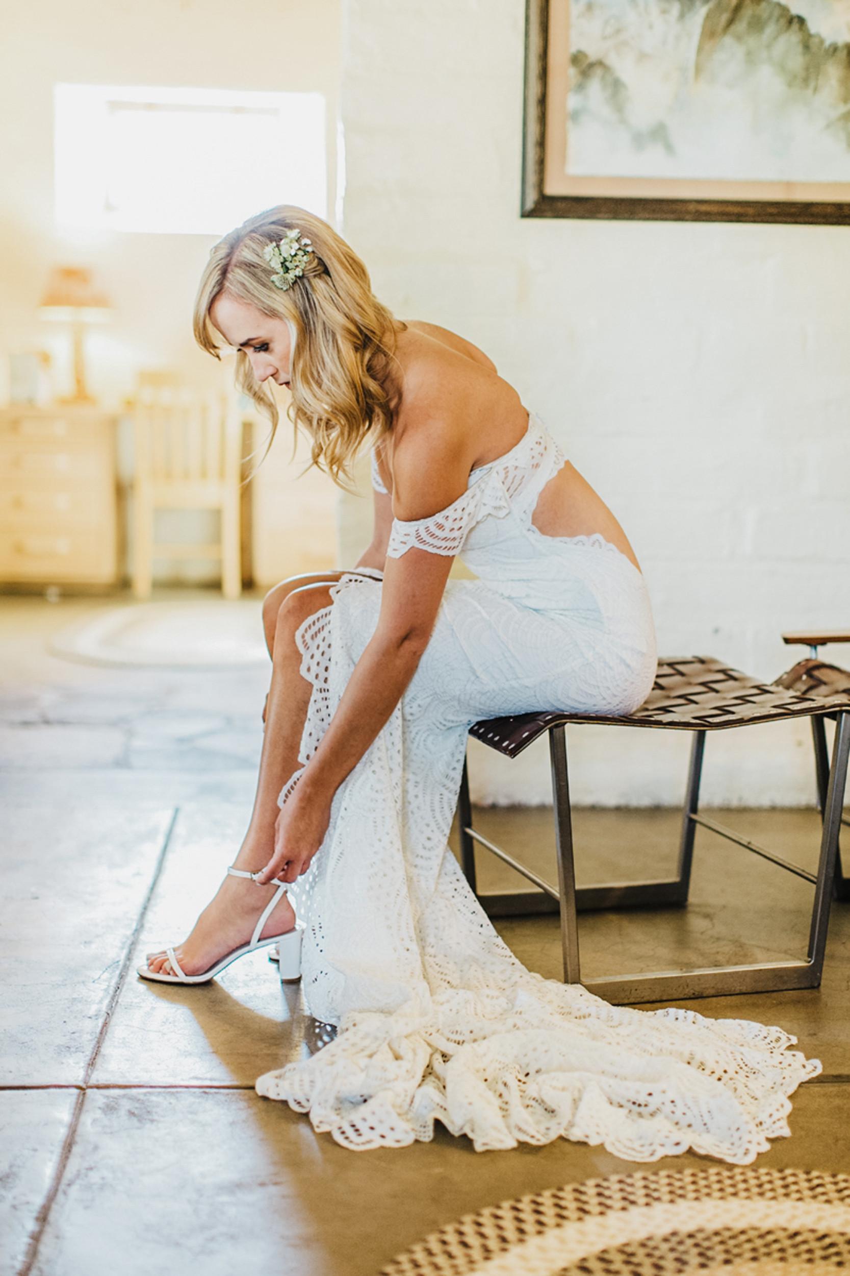grace loves lace bride putting shoes on