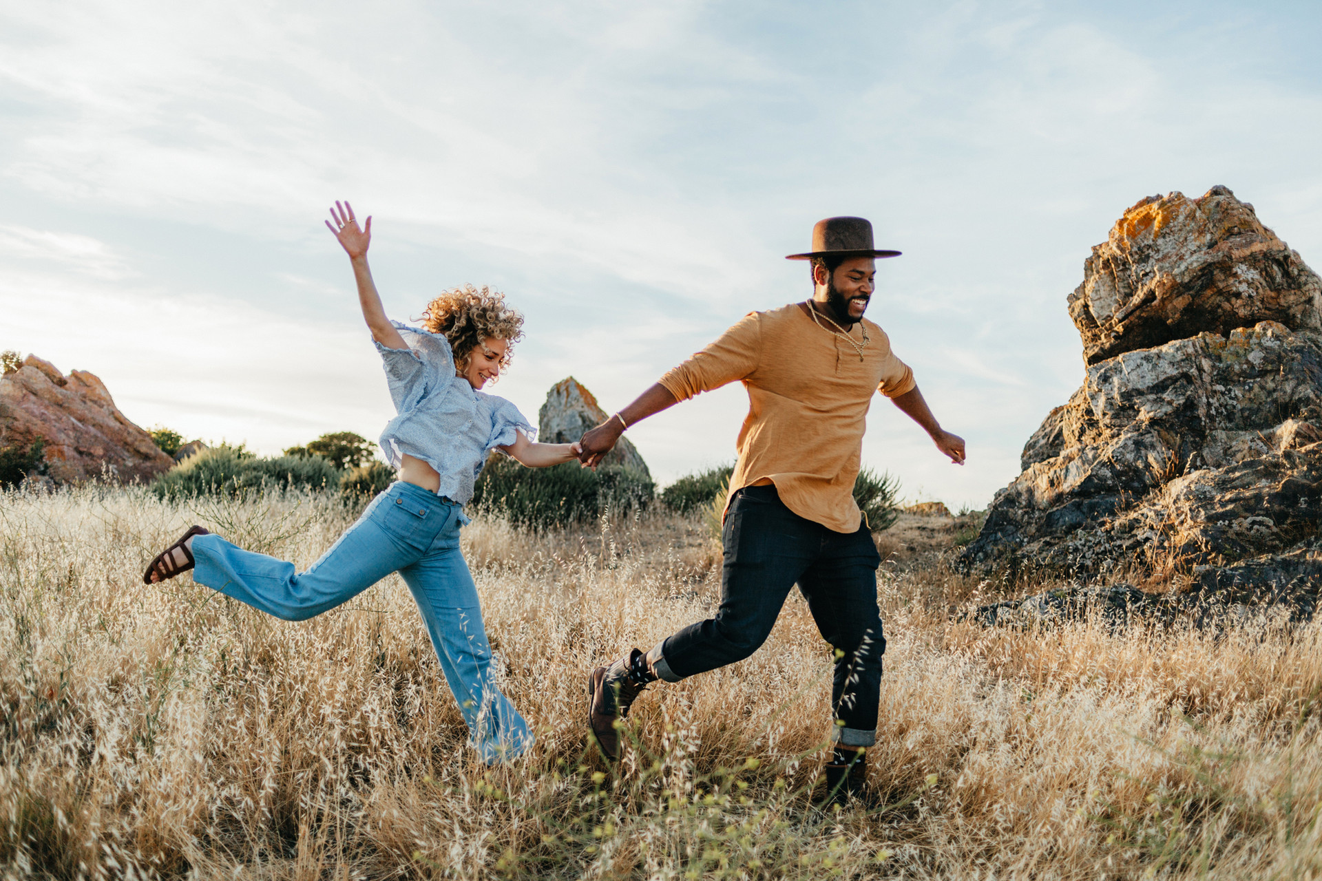 couple running through field engagement photography