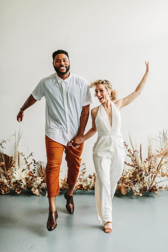 bride and groom jumping bridal jumpsuit