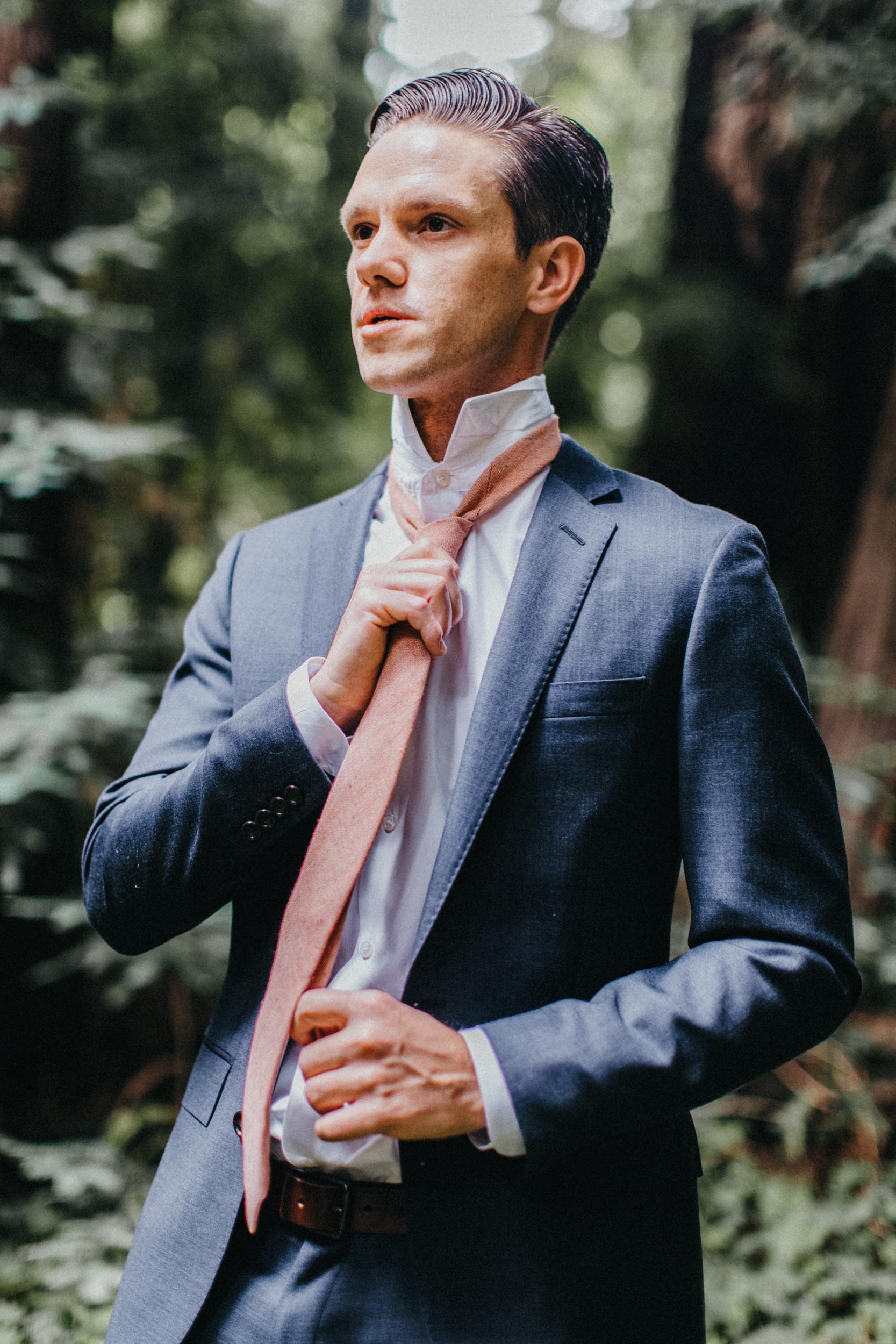 groom fixing tie in redwood forest