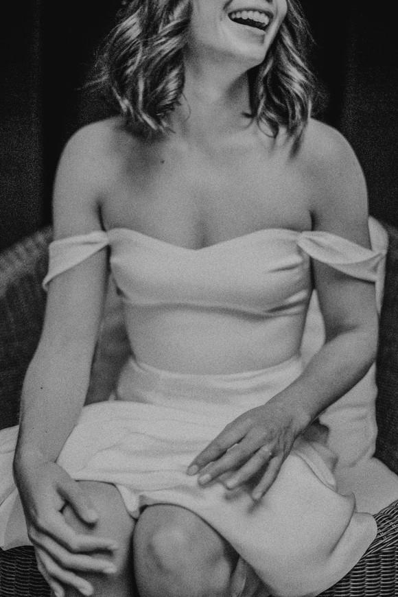 bride laughing off the shoulder reformation dress