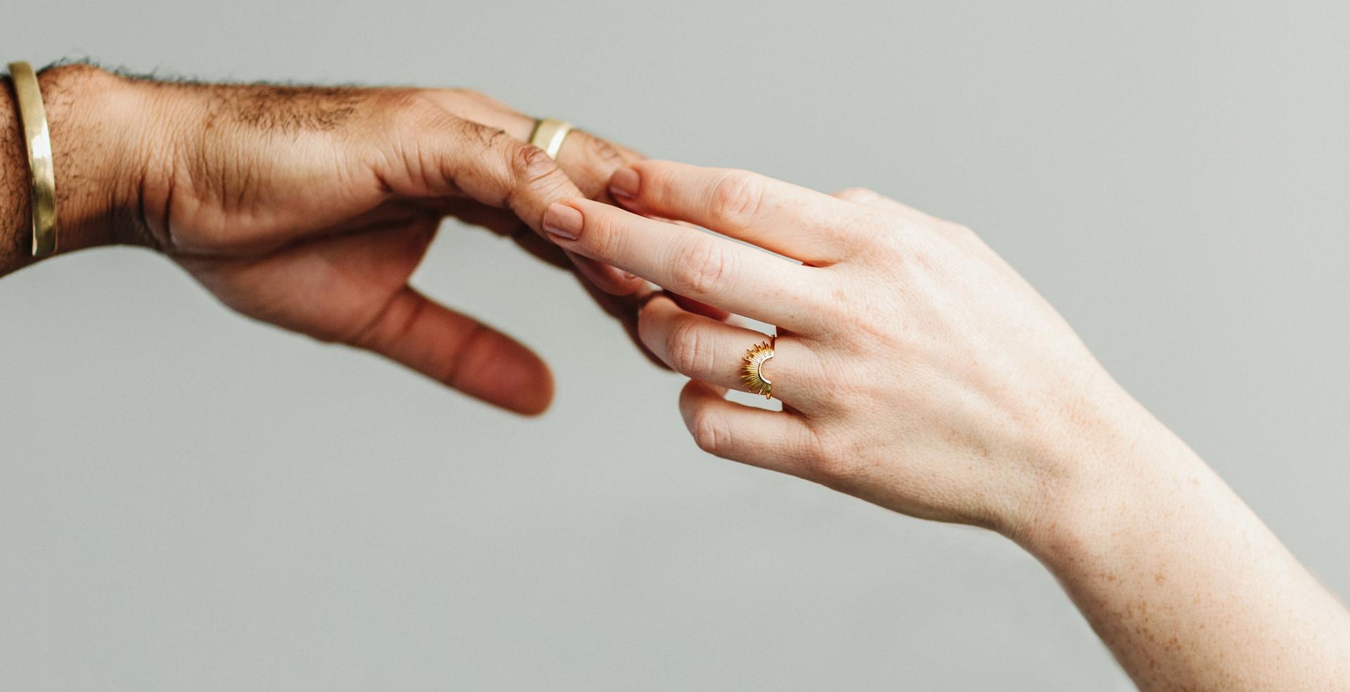 black hand touching white hand with sunburst engagement ring